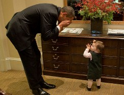 "30 Oct 2009, Washington, DC, USA --- ""Washington, DC - October 30, 2009 -- United States President Barack Obama plays peek-a-boo with Maeve Beliveau, the daughter of Director of Advance Emmett Beliveau, in the Outer Oval Office, October 30, 2009. Mandatory Credit: Pete Souza - White House via CNP"" --- Image by © Pete Souza/White House/Handout/CNP/Corbis"